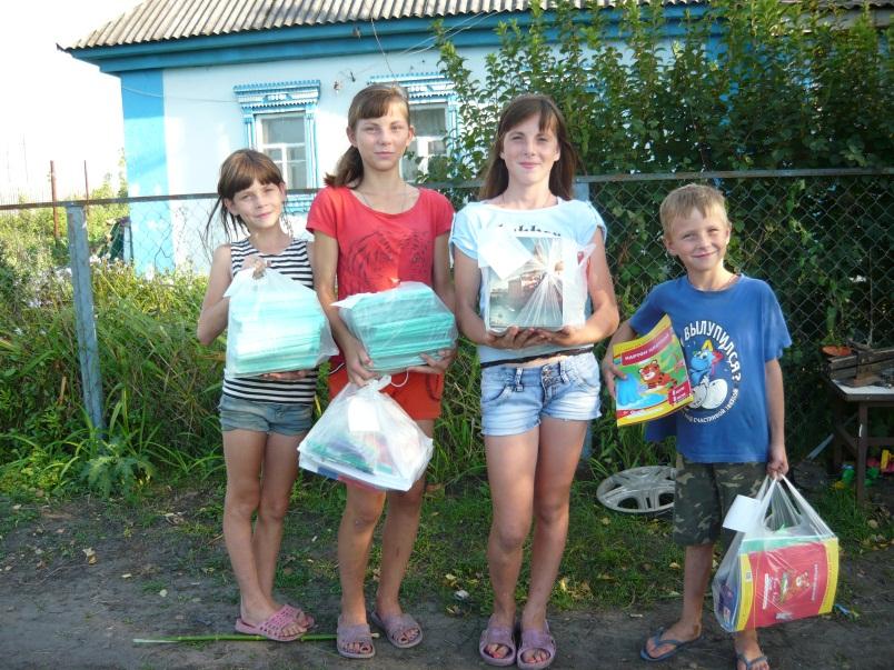 На этой фотографии дети из семьи, в которой девять детей. Получившие подарок школьники веселые и довольные, а сегодня в семье горе — трагически погиб отец.